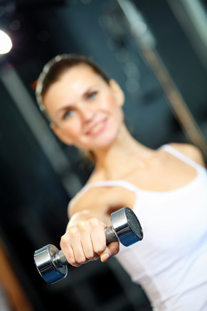 front raise: Image of fitness girl in gym exercising with dumbbells Stock Photo