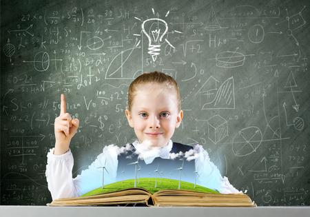 schoolkid search: Colegiala mirando en el libro abierto con dibujos