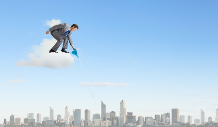 Young businessman standing on cloud and watering something below Stock Photo