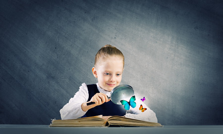 Little school girl examining butterfly with magnifying glass photo