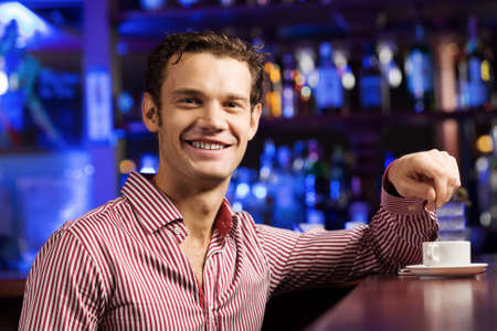 Young handsome man in casual sitting at bar photo