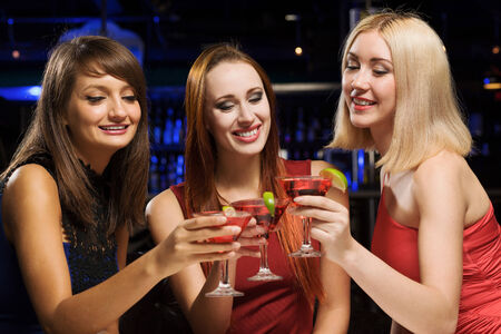 Three elegant ladies with cocktails at night club photo