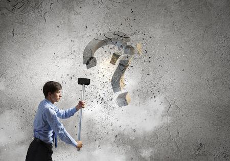 Young pretty businessman crashing stone question symbol