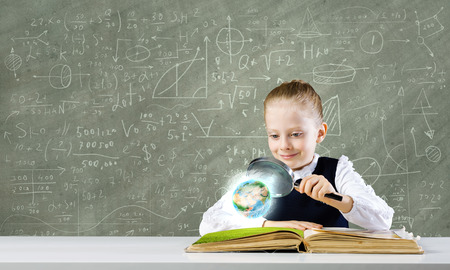 Schoolgirl examining opened book with magnifying glass  Elements of this image are furnished by NASA photo