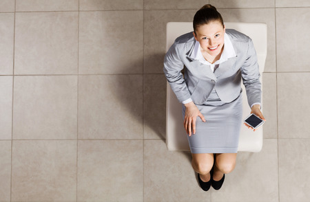 Top view of businesswoman sitting on chair with mobilephone in hand photo