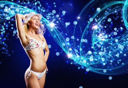 Young woman in white bikini dancing against color background photo