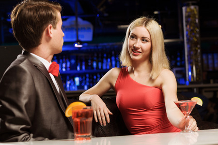 Young handsome man in bar accompanied by elegant lady photo