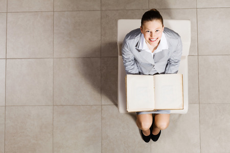 Top view of businesswoman sitting in chair and reading book photo