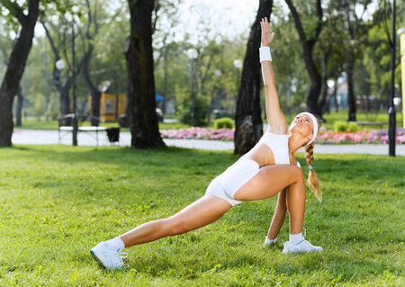 Young sport woman in white stretching in park Stock Photo