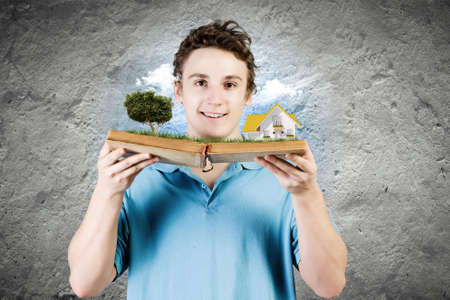 Young man in casual holding opened book with green tree photo