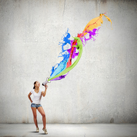 oratoria: Mujer joven al hablar casual en el megáfono con salpicaduras de colores volando Foto de archivo
