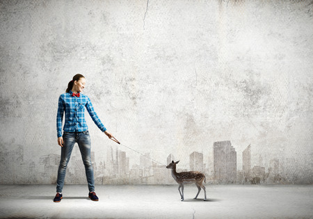 positivism: Young woman in casual holding fawn on lead