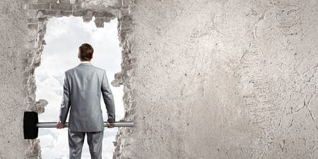 construction management: Young businessman with big hammer against wall