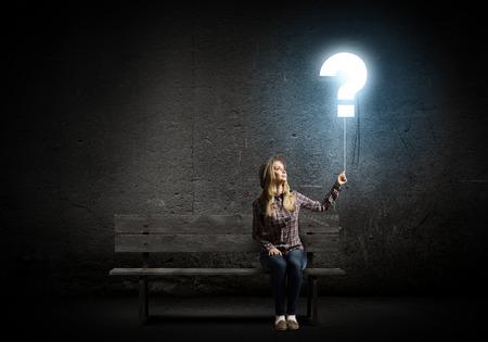 signo de interrogacion: Mujer joven en globo holding informal forma de signo de interrogación