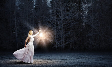 Young woman in white long dress walking in night wood photo