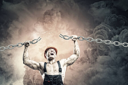 Strong man in uniform tearing metal chain with hands photo