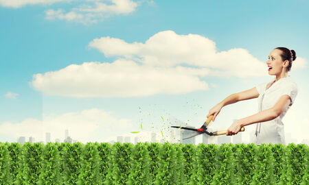 Young attractive businesswoman cutting green lawn  Greenery concept photo