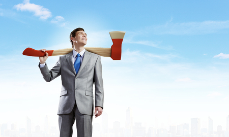 Young businessman holding big axe on shoulder photo