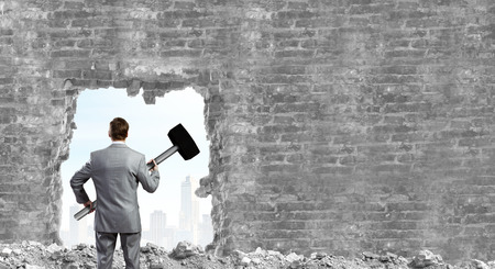 Young businessman with big hammer against wall