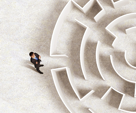 complexity: Top view of successful businessman standing near the entrance of labyrinth Stock Photo