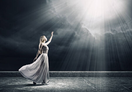 Young woman in white long dress reaching to light photo