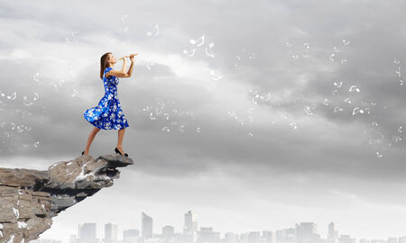 Young woman in blue dress on edge of rock playing fife Stock Photo