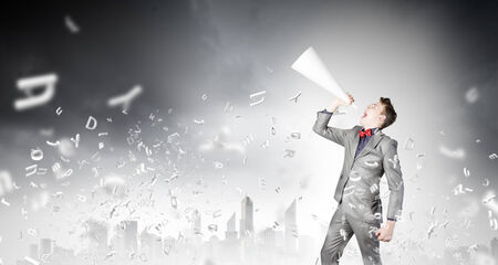 speaking trumpet: Young excited businessman screaming in paper trumpet