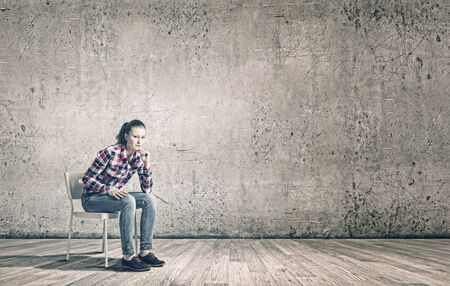 Young woman sitting on chair in empty room photo