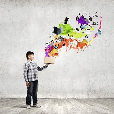 Cute boy splashing colorful paint from carton box photo