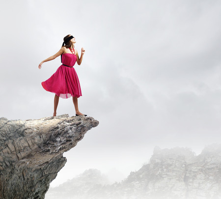 Woman in red dress standing on edge of rock