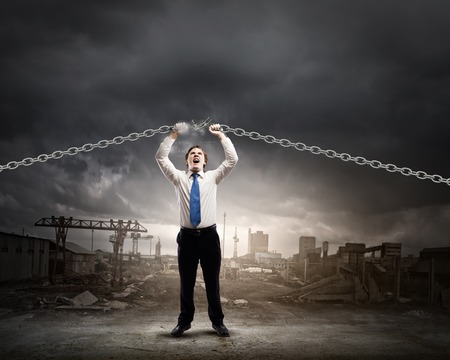 Young furious businessman breaking metal chain with hands photo