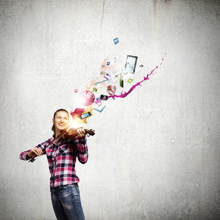 Young pretty woman in casual playing on violin photo