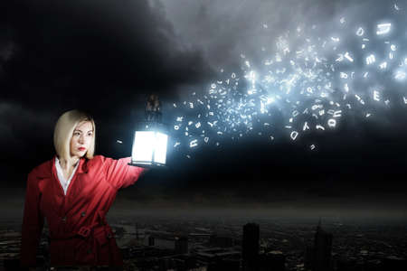 Young blond woman in red cloak with lantern photo