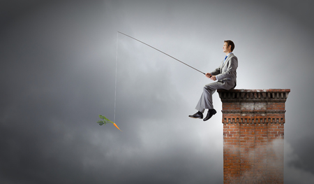 Businessman sitting on top of building and fishing with rod photo