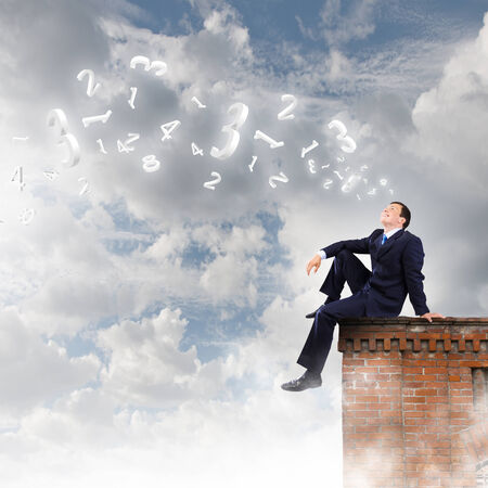 Young successful businessman sitting on top of building photo