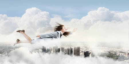 Young pretty businesswoman flying in sky above city photo