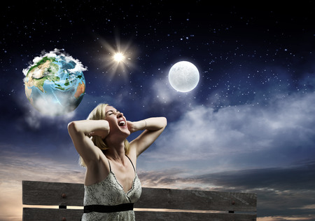 Young woman sitting on bench closing ears with palms and screaming  Elements of this image are furnished by NASA photo