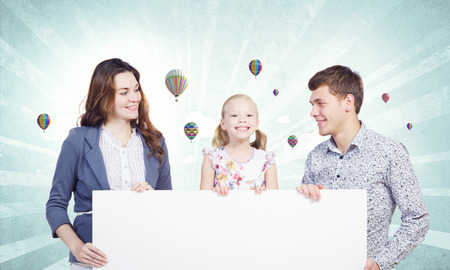 Young happy family with white blank banner  Place for text photo