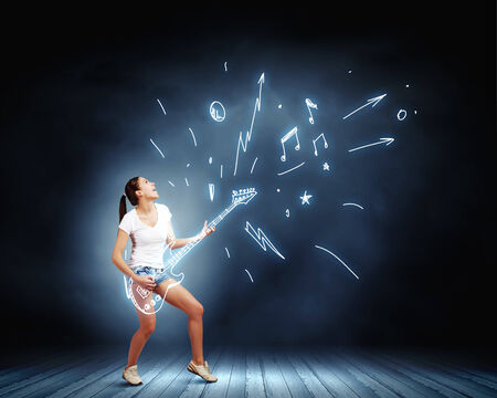 Young girl in shorts playing on imaginary guitar Фото со стока