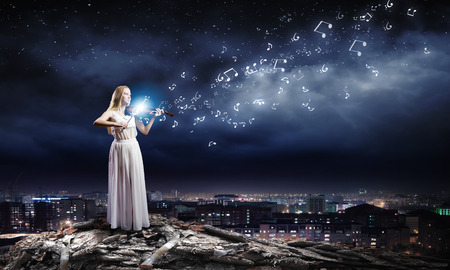 Young woman in white dress playing violin at night photo