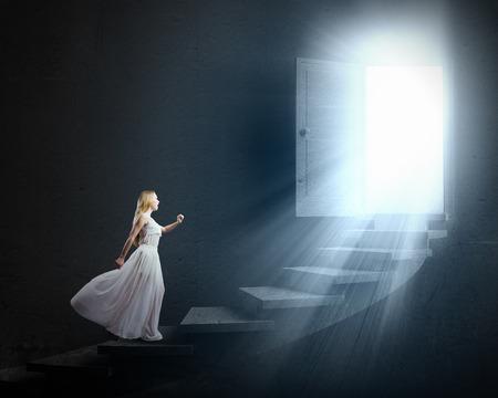 階段を歩いて白いドレスの若い女性