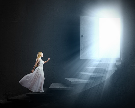 Young woman in white long dress walking up the staircase photo