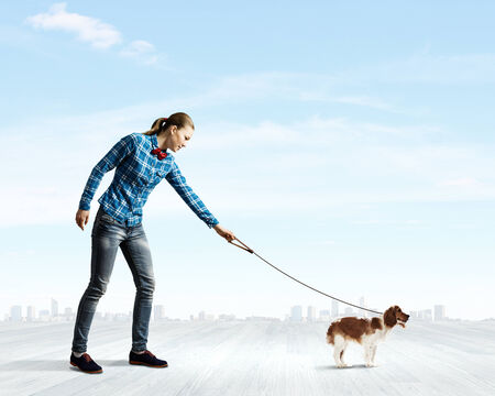lead rope: Young woman in casual walking with dog on lead