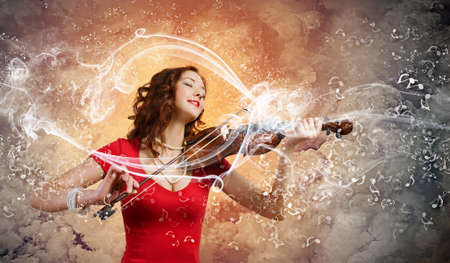Young attractive woman in red dress playing violin photo