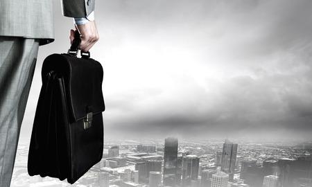 手にスーツケースを持ったビジネスマンを背面します。