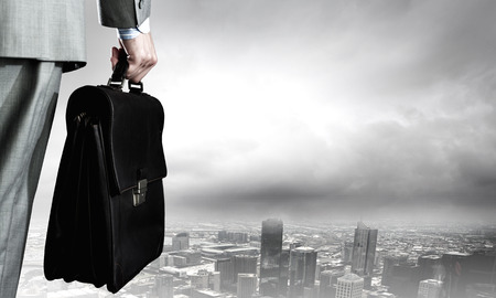 executive job search: Back view of businessman with suitcase in hand Stock Photo