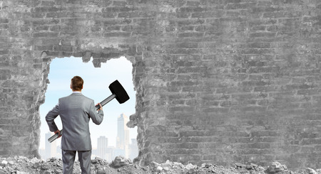 Young businessman with big hammer against wall photo