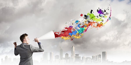 speaking trumpet: Young businessman speaking in trumpet and colorful splashes flying out