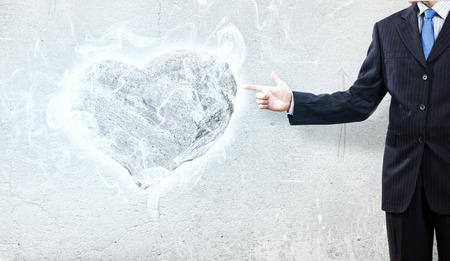 brute: Businessman pointing at stone in shape of heart Stock Photo