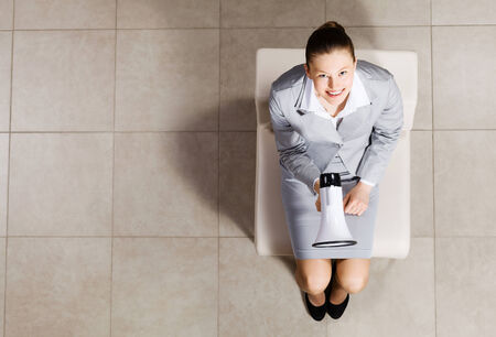 Top view of businesswoman sitting on chair with megaphone in hand photo